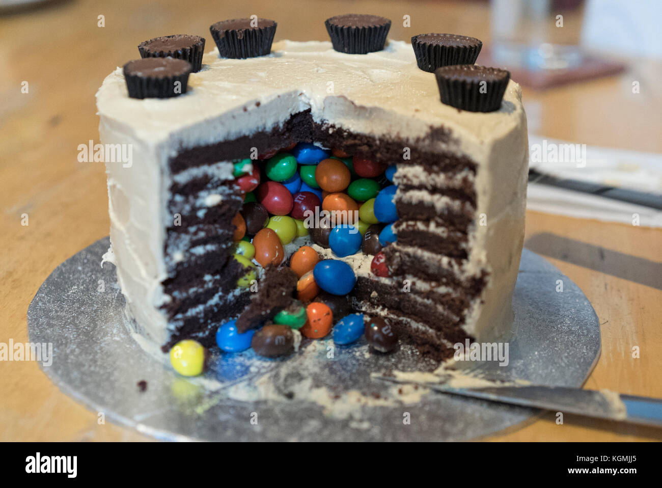 Ornate fancy birthday cake comprising chocolate sponge with peanut icing and enclosing peanut M&M candies inside - Stock Image