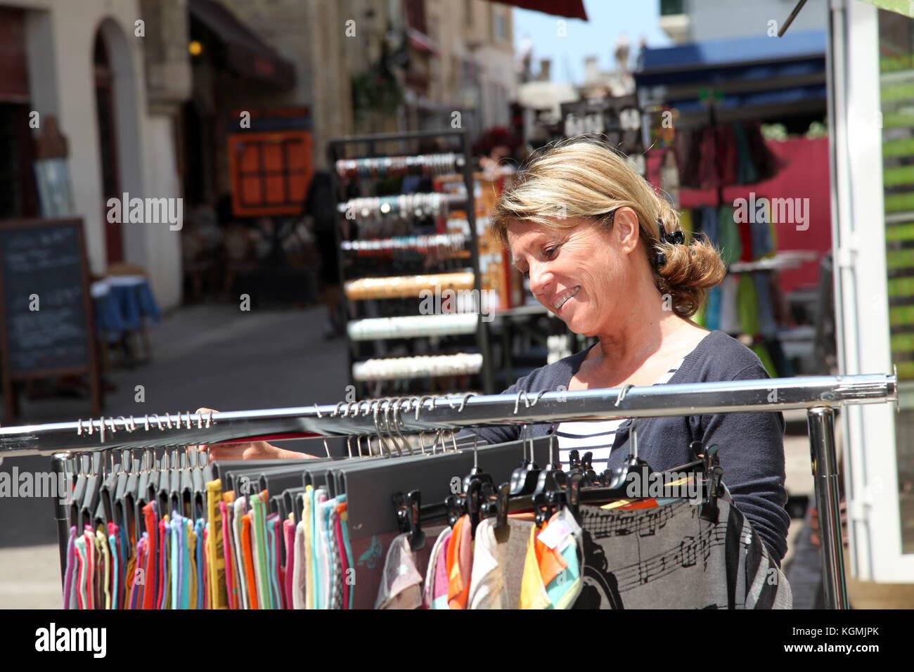 Mature woman doing shopping in seaside resort shops - Stock Image