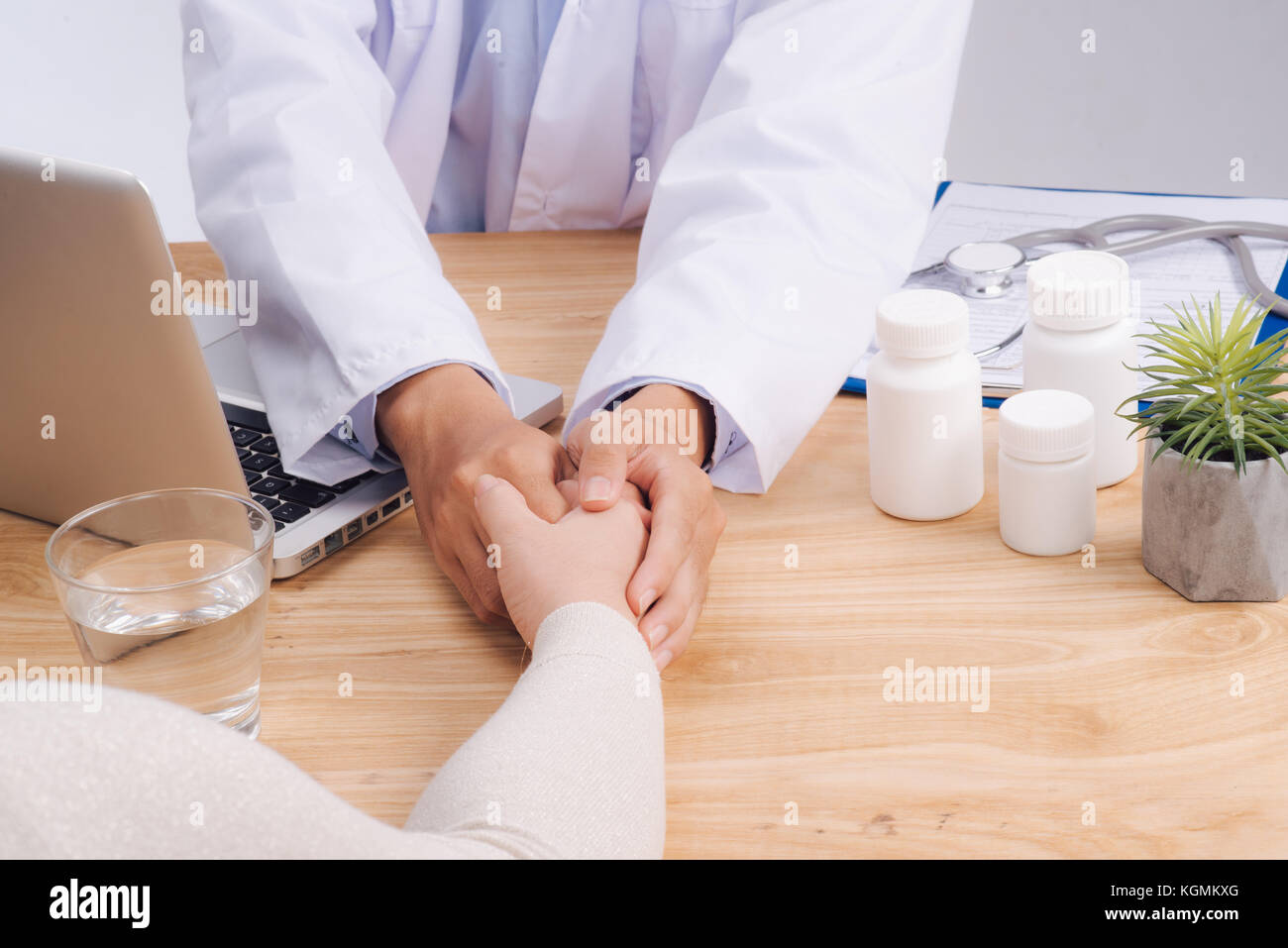 Friendly doctor hands holding patient hand sitting at the desk for encouragement, empathy, cheering and support - Stock Image