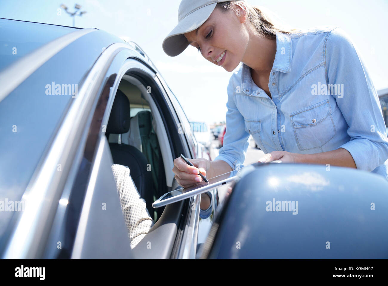 Woman stopping car driver for customer survey - Stock Image