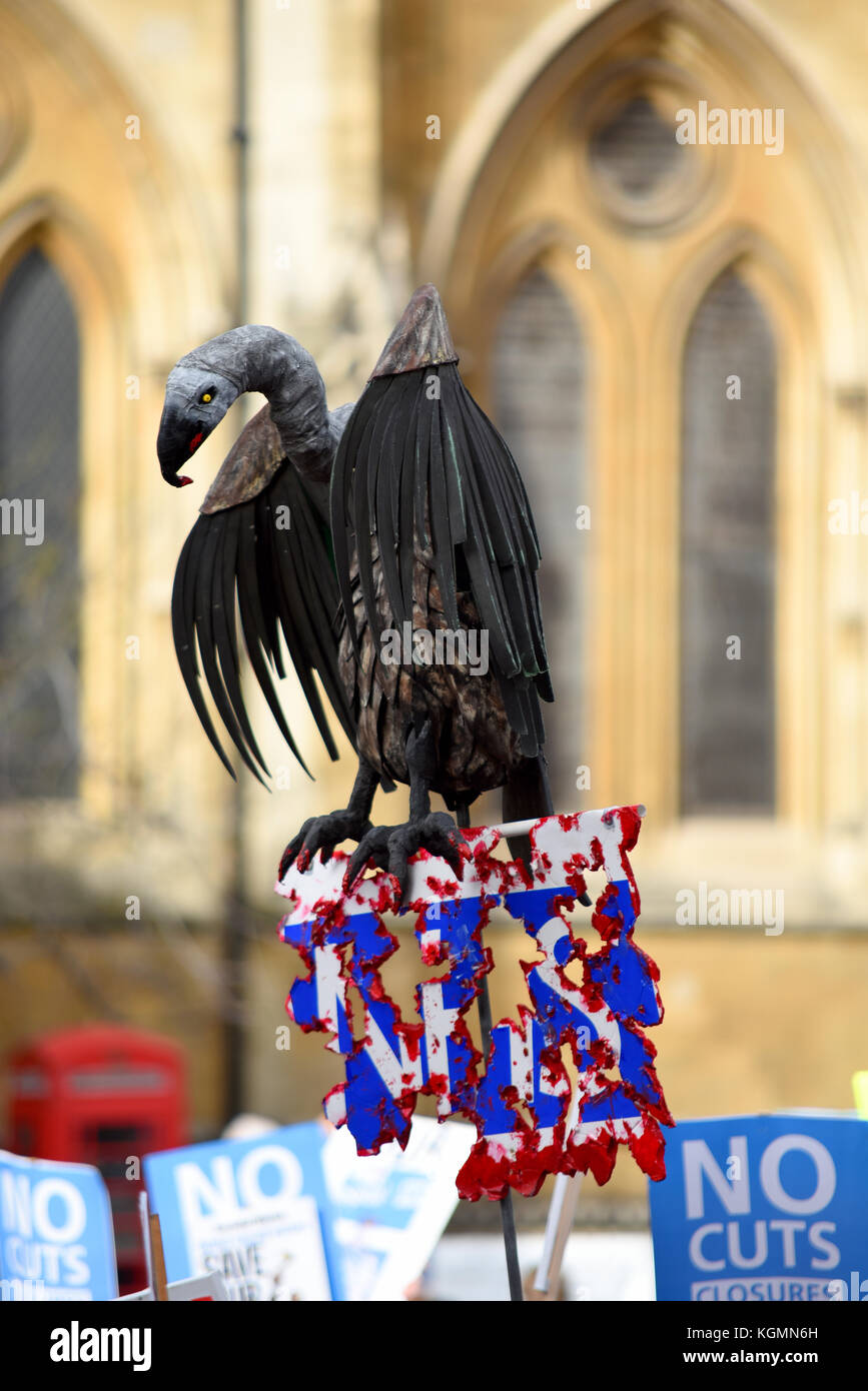 Vulture caricature on placard during Our NHS protest demonstration rally march against alleged UK Tory Conservative - Stock Image