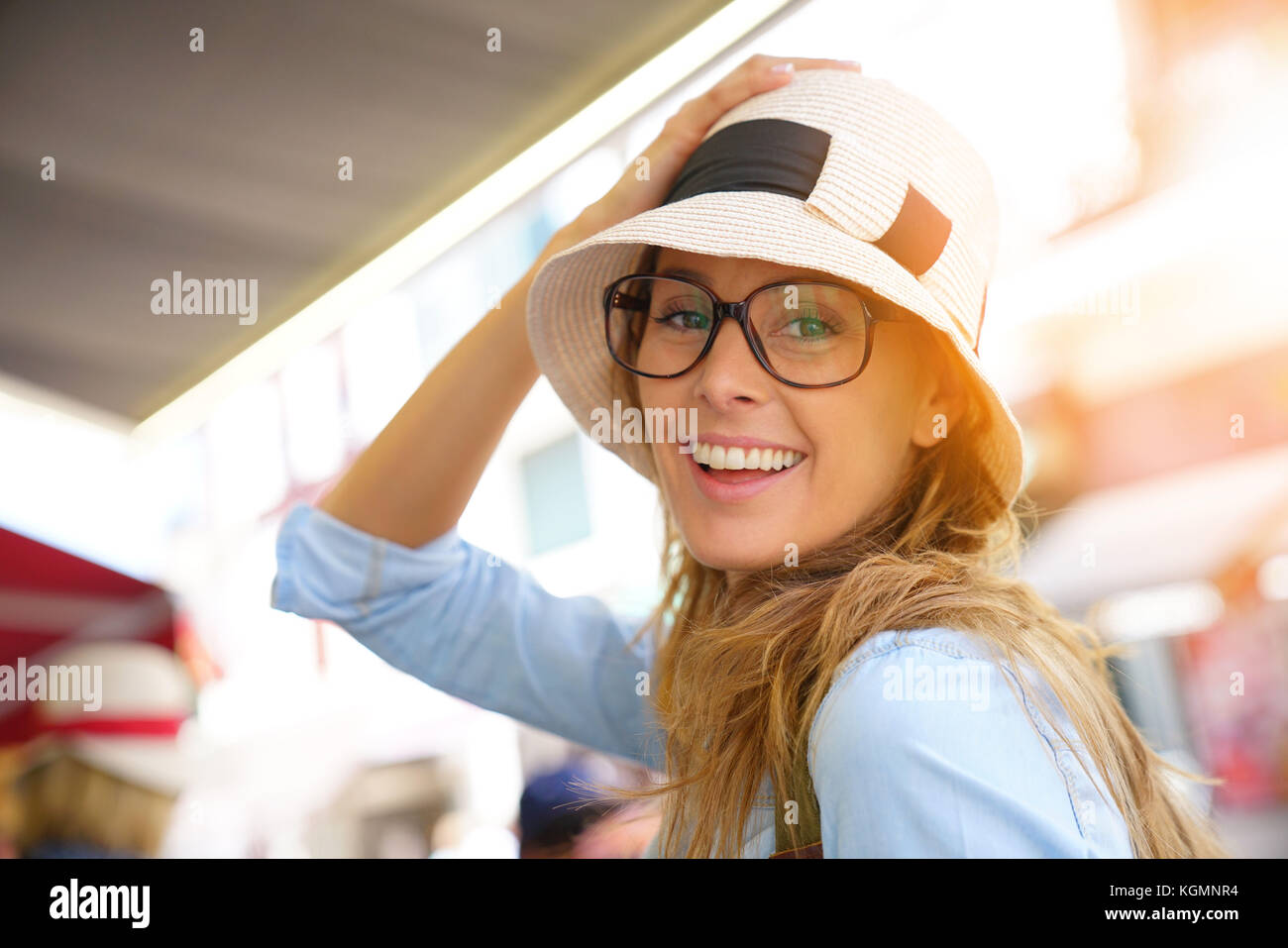 Portrait of beautiful woman trying summer hat on - Stock Image