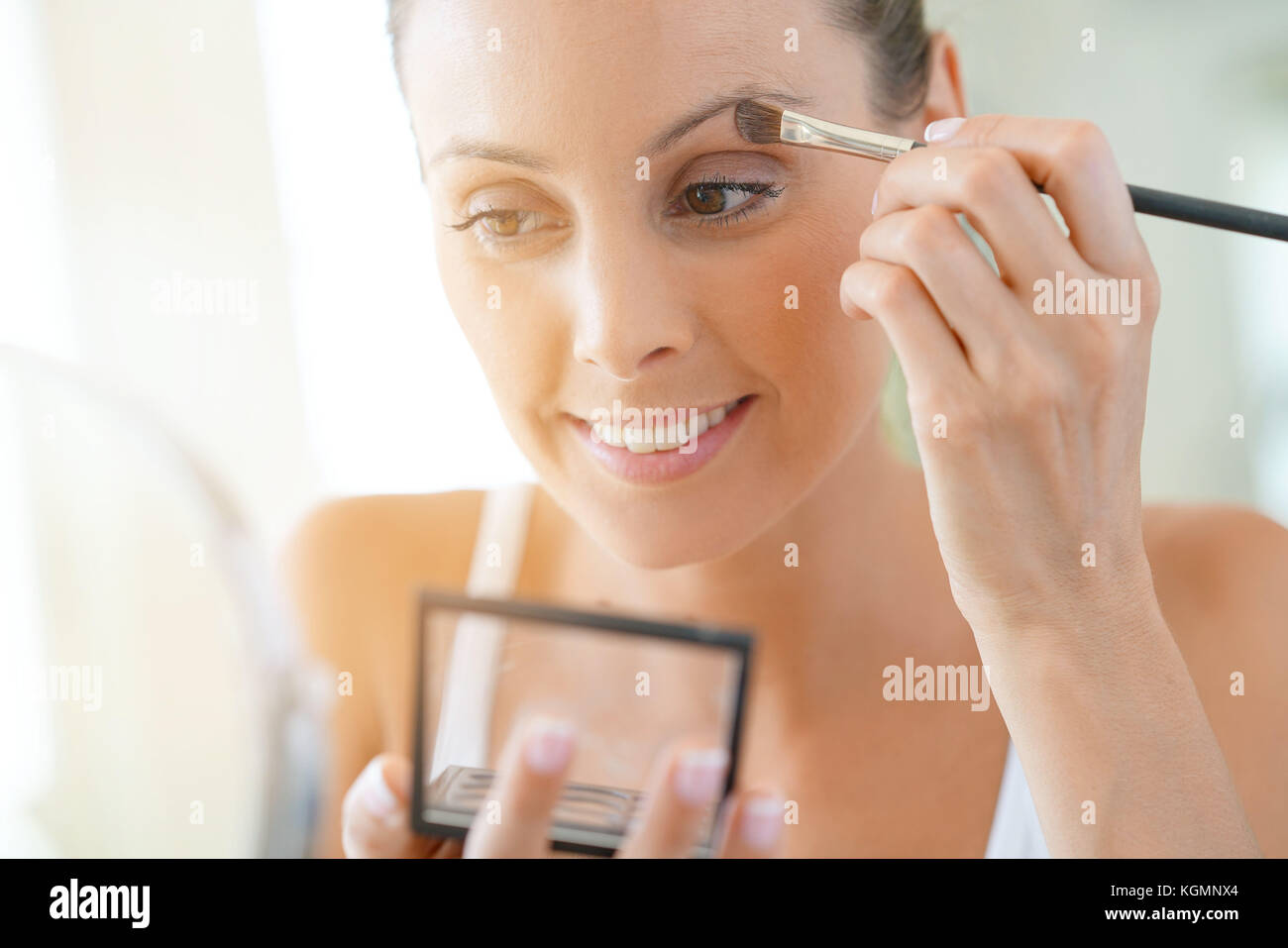 Young woman applying eyeshadow on - Stock Image