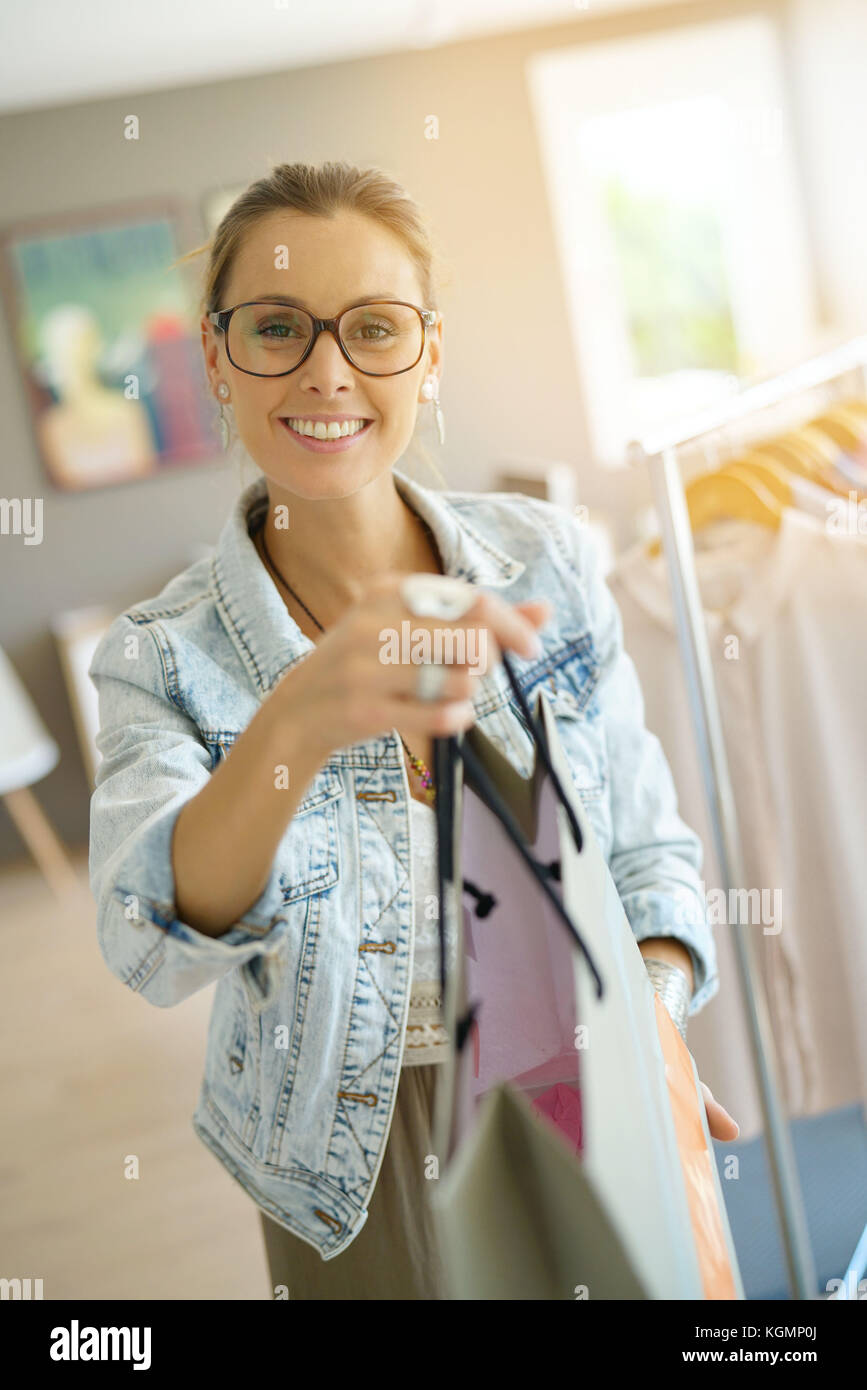 Cheerful salesperson handing shopping bag to customer - Stock Image