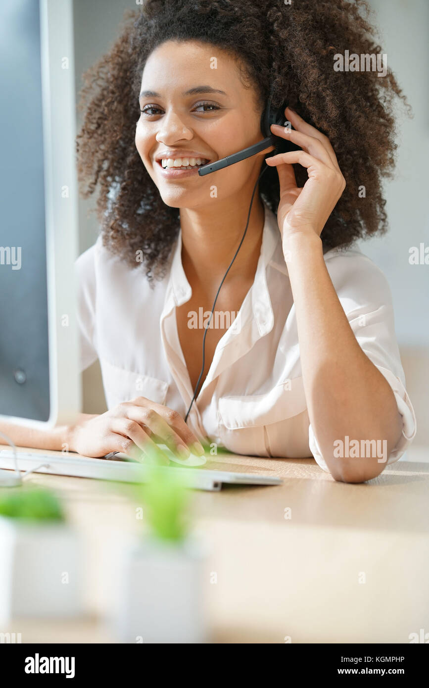 Portrait of customer service assistant talking on phone - Stock Image