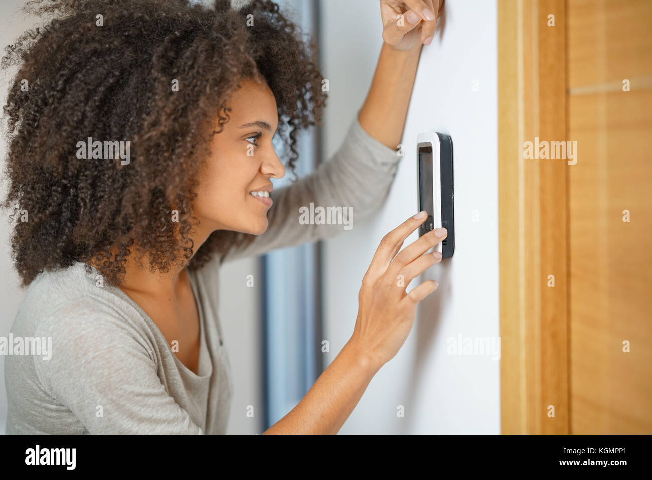 Woman controlling home appliances with central electronic device - Stock Image
