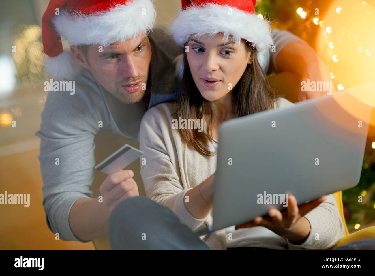 Couple buying Christmas gifts online with laptop - Stock Image
