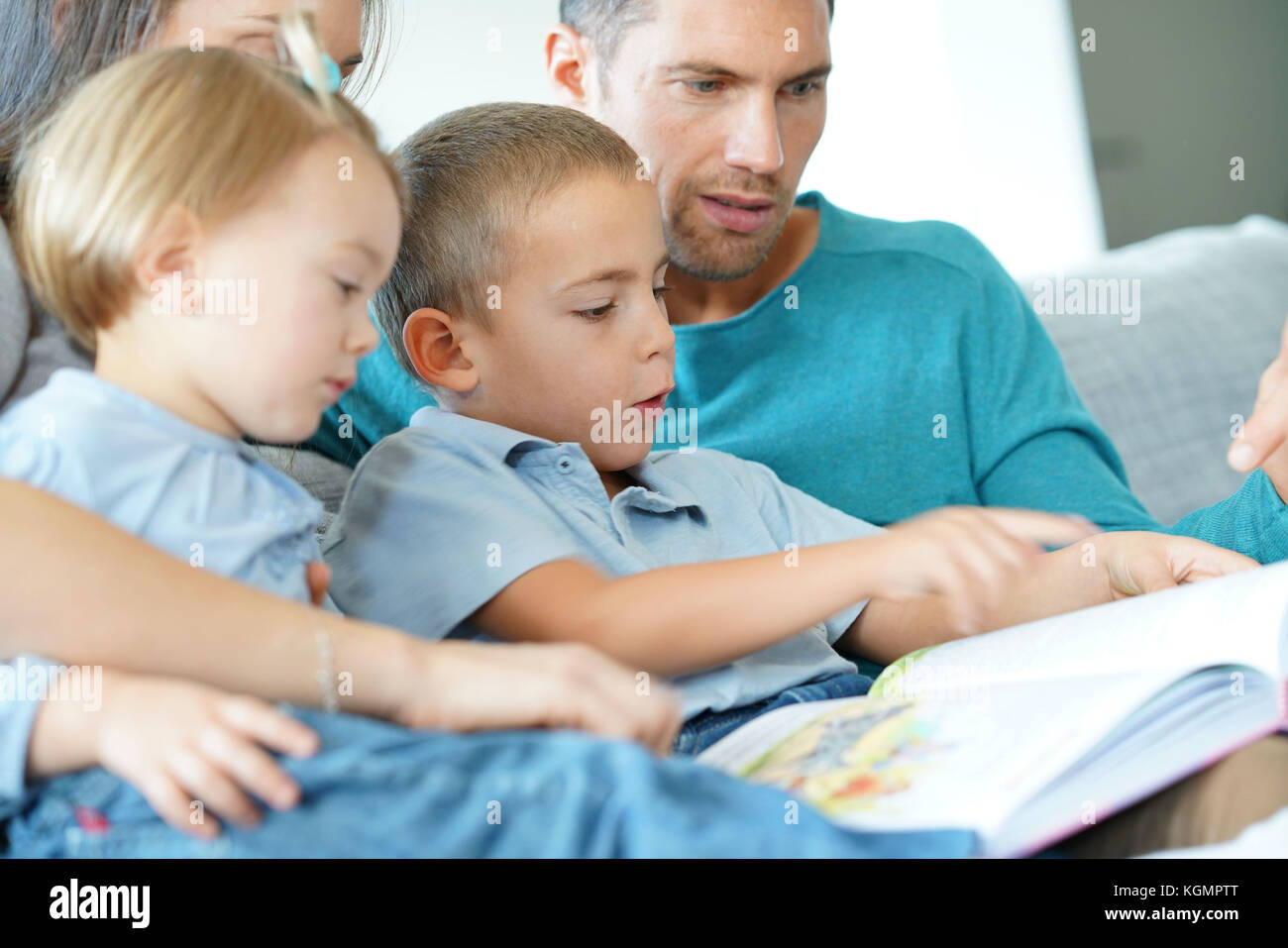 Family sitting on sofa reading book with kids Stock Photo