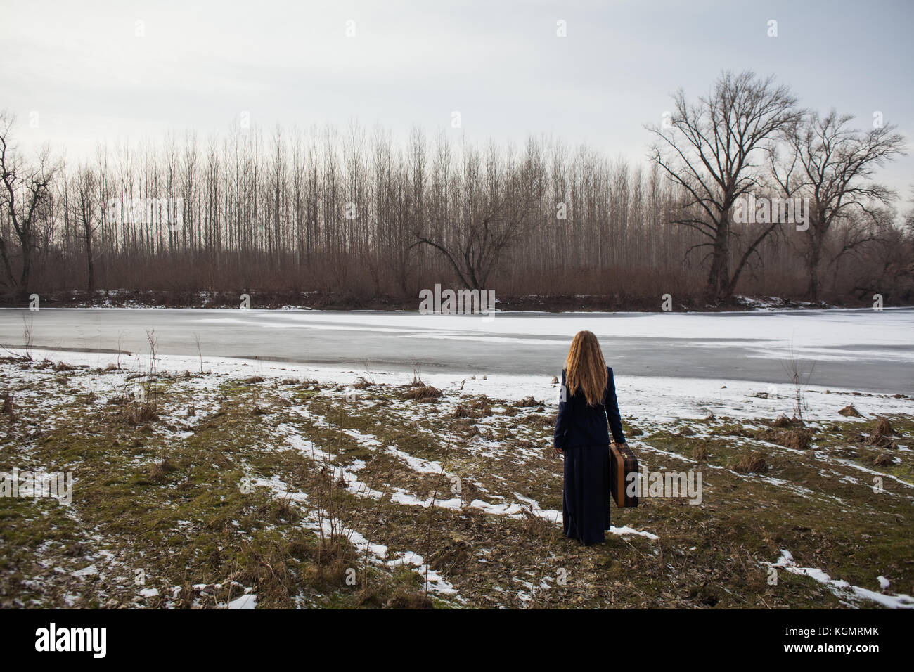 Woman standing near river with old suitcase and looking for a way to go - Stock Image