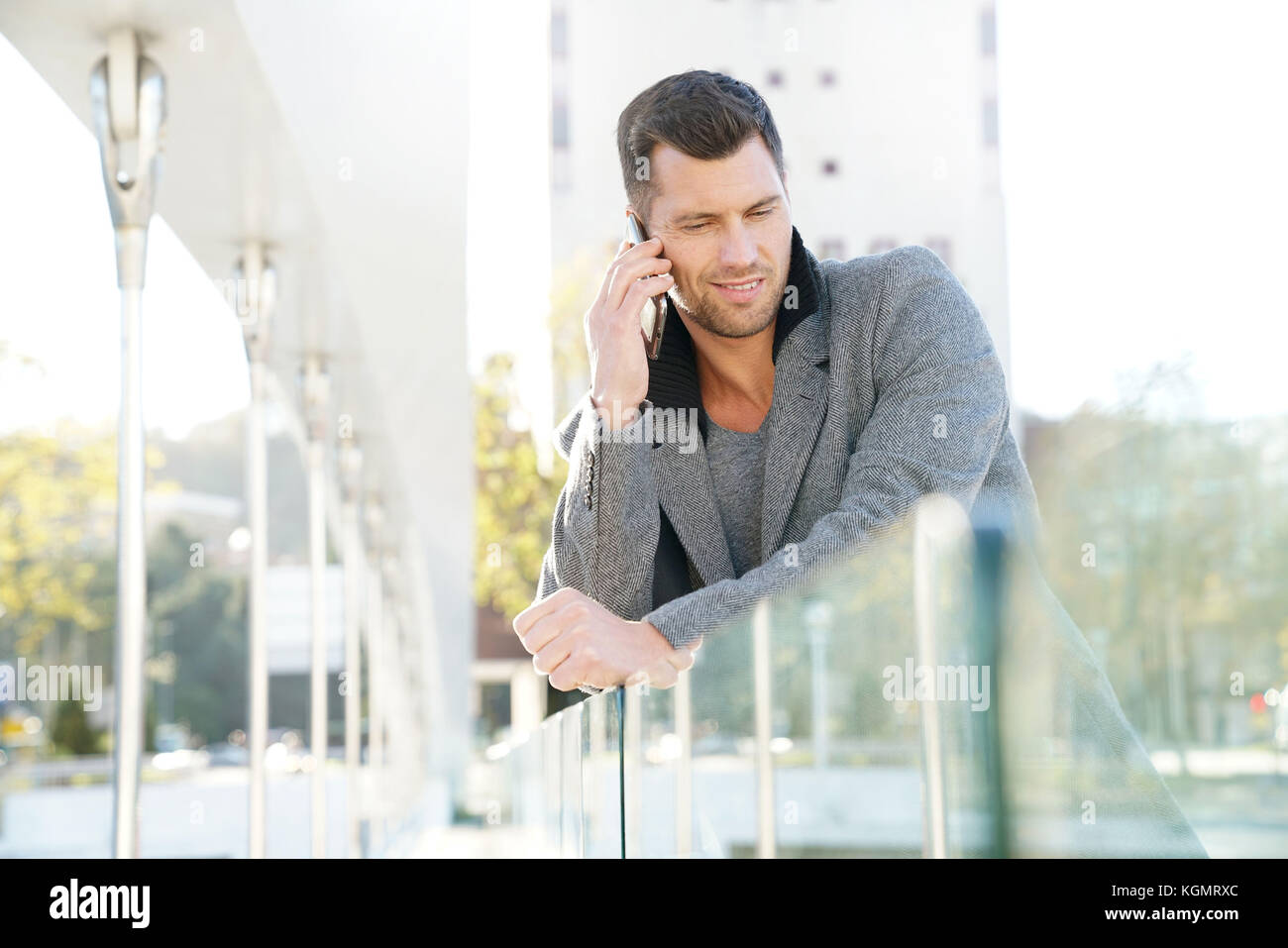 Handsome businessman talking on phone outside - Stock Image