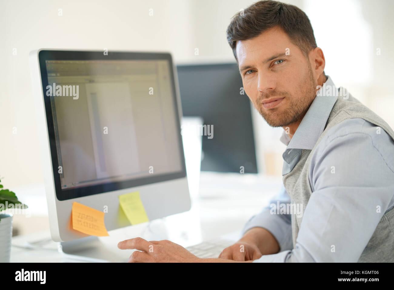 Handsome businessman working on desktop computer in office Stock Photo