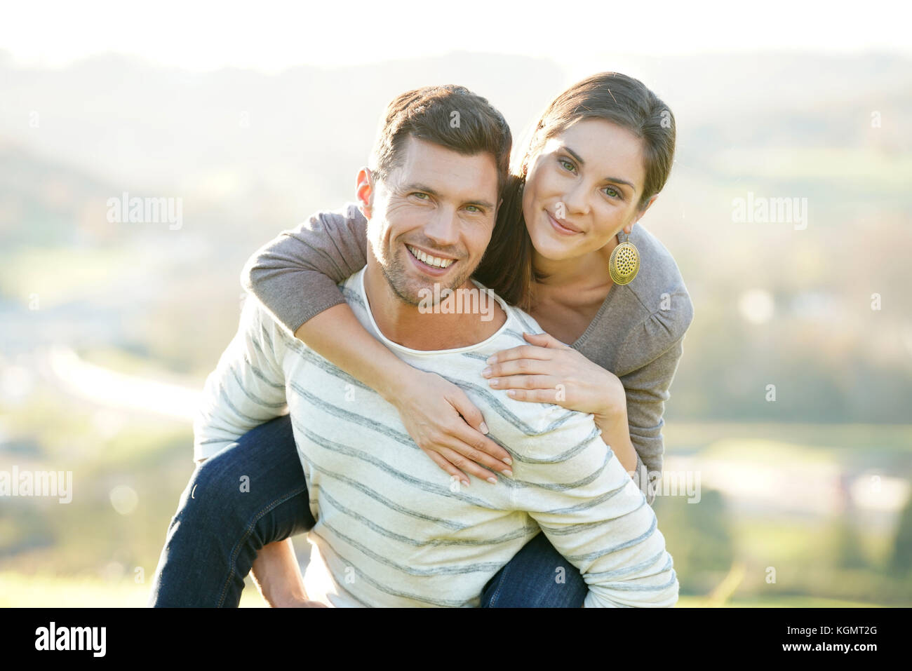 Portrait of cheerful man giving piggyback ride to girlfriend - Stock Image