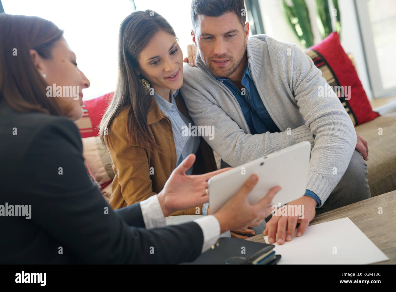 Real estate agent showing house project on tablet to clients - Stock Image