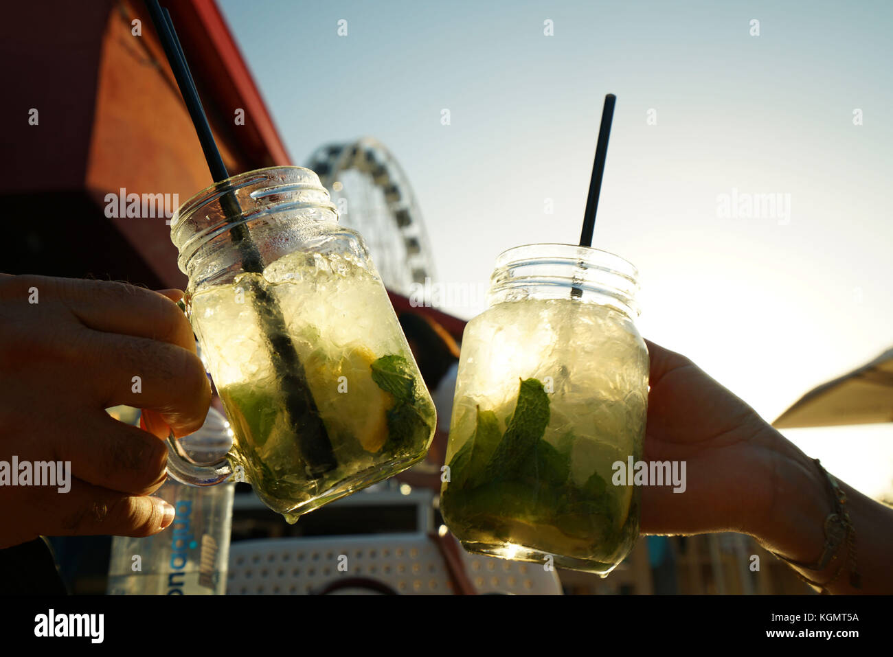 Closeup of people cheering with mojito drinks - Stock Image