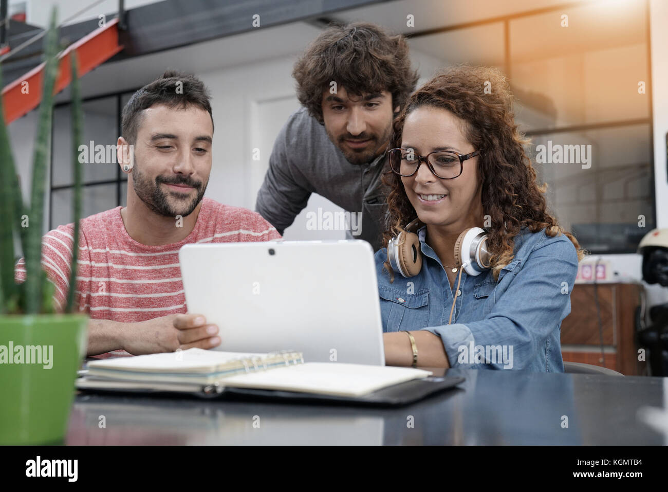 Young entrepreneurs working on digital tablet - Stock Image