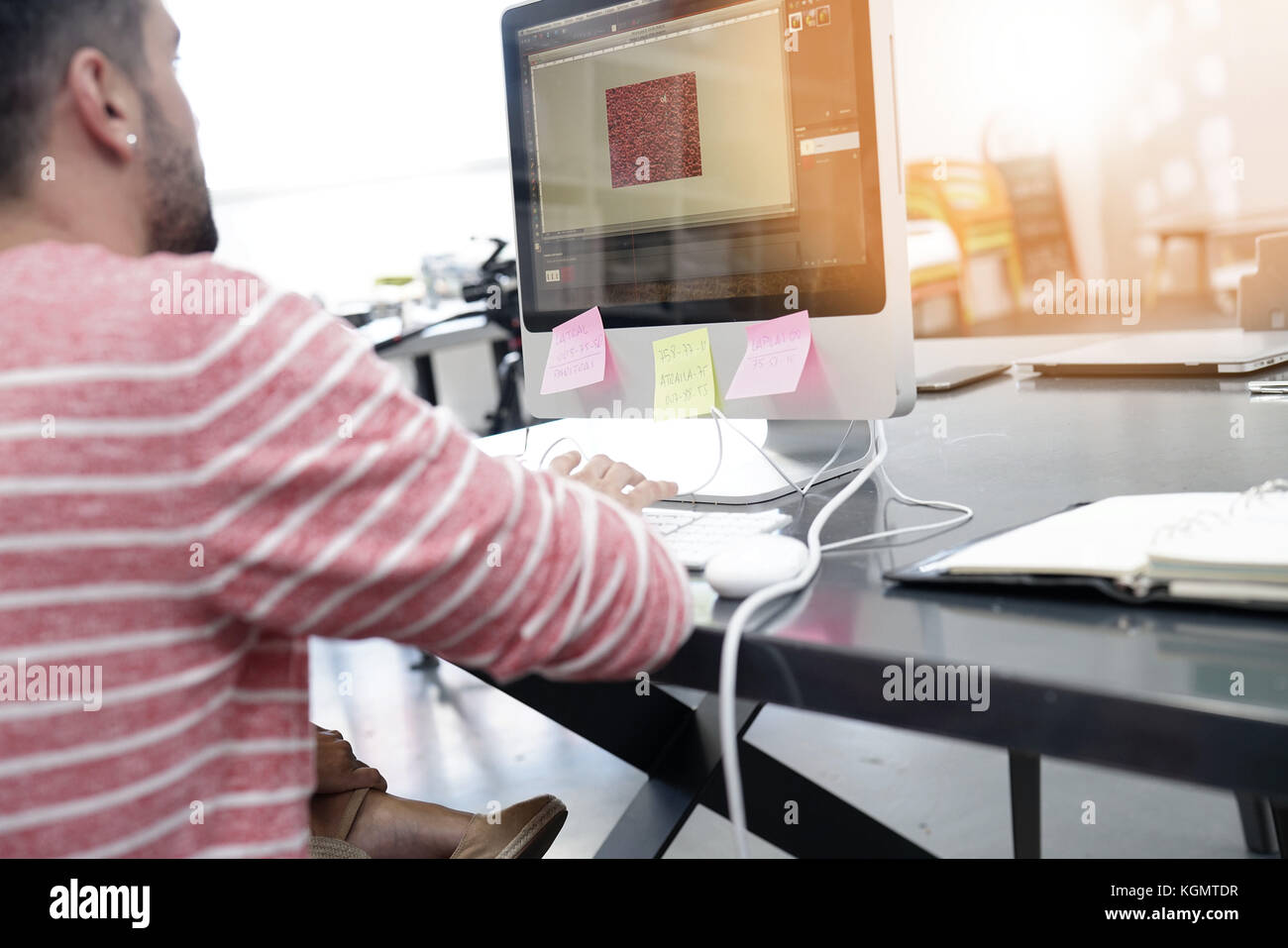 back view of man working on desktop in office - Stock Image