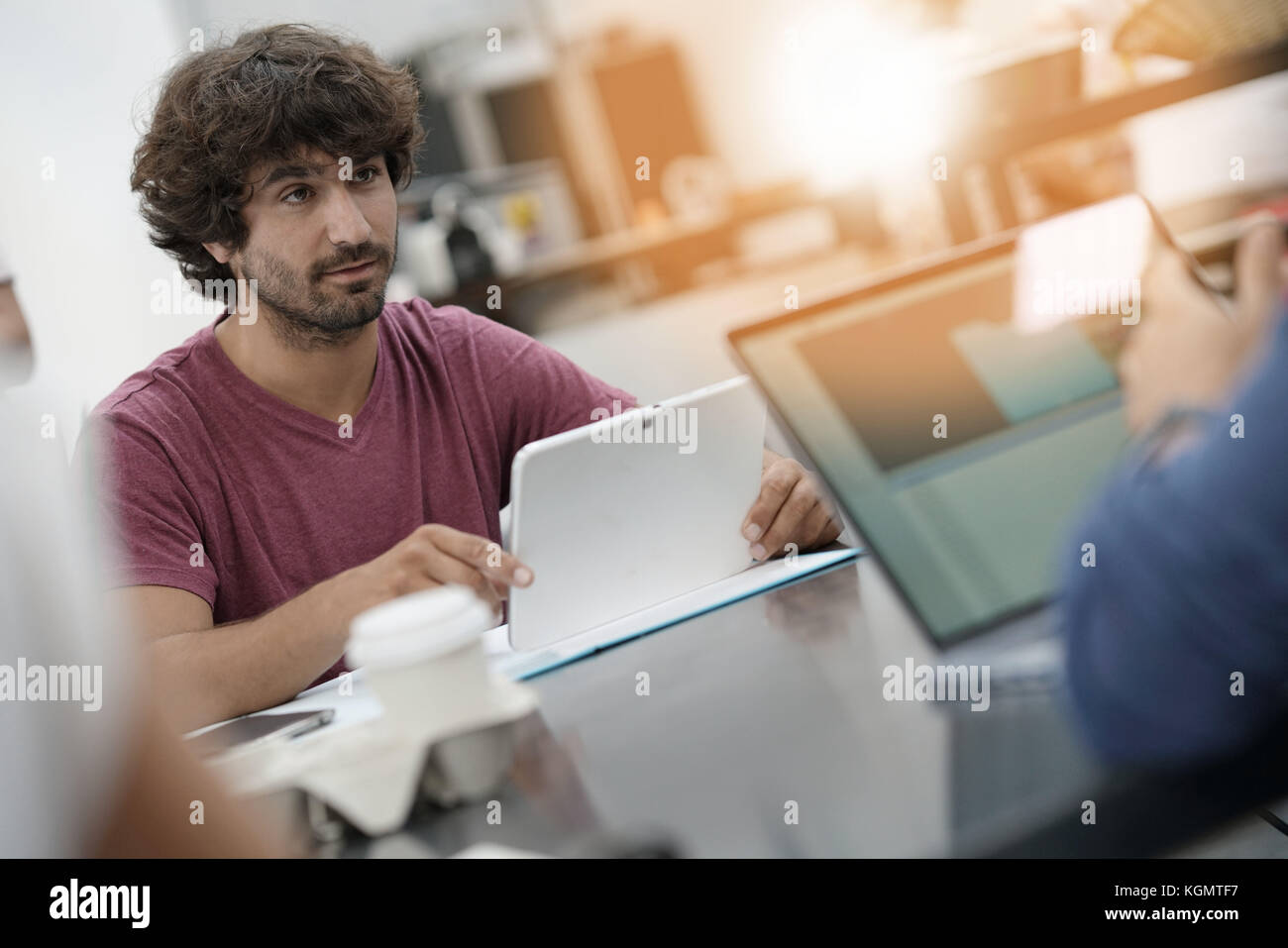 Young entrepreneur man working in office on laptop - Stock Image