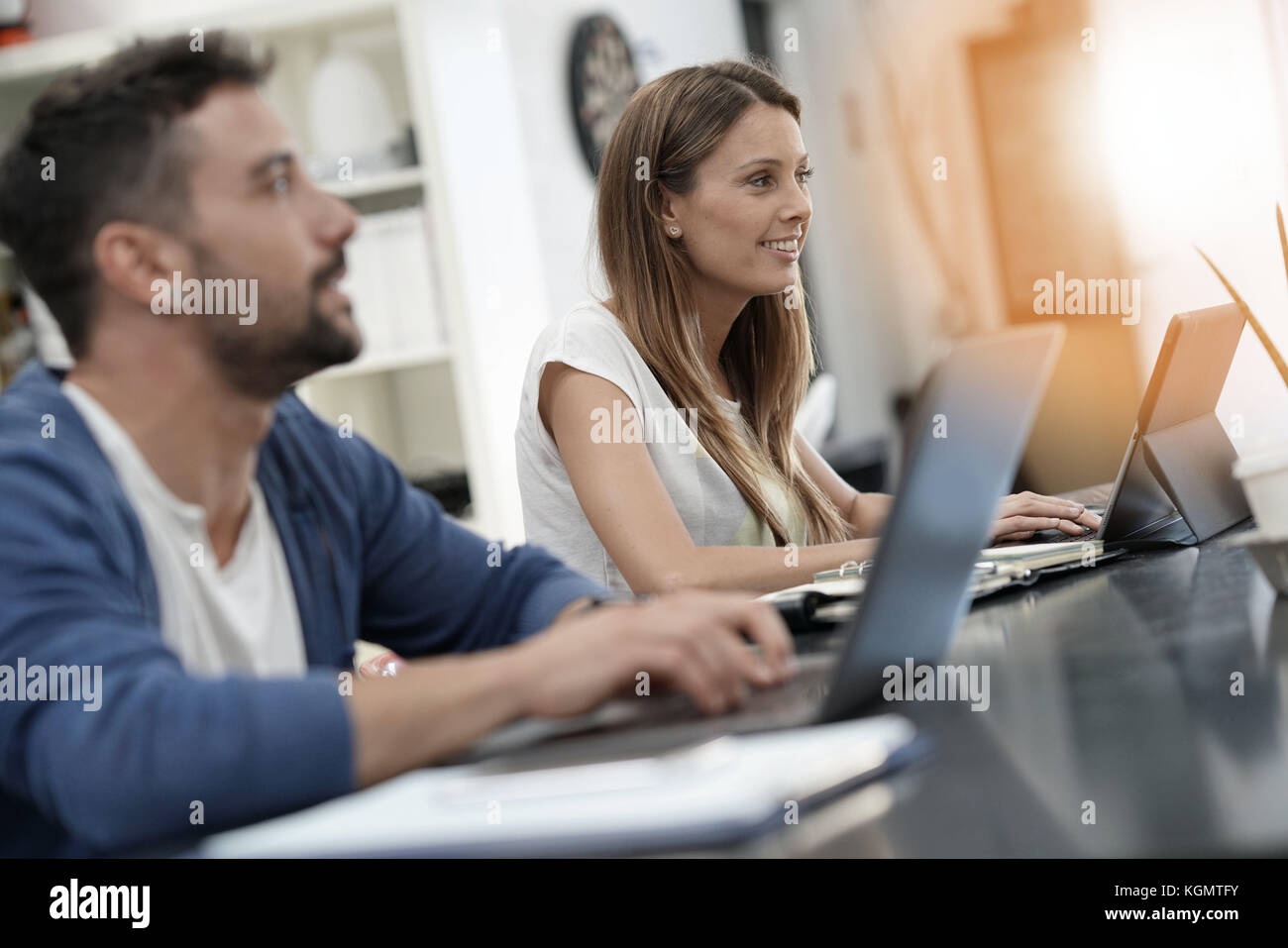 Trendy young people working in co-working office - Stock Image