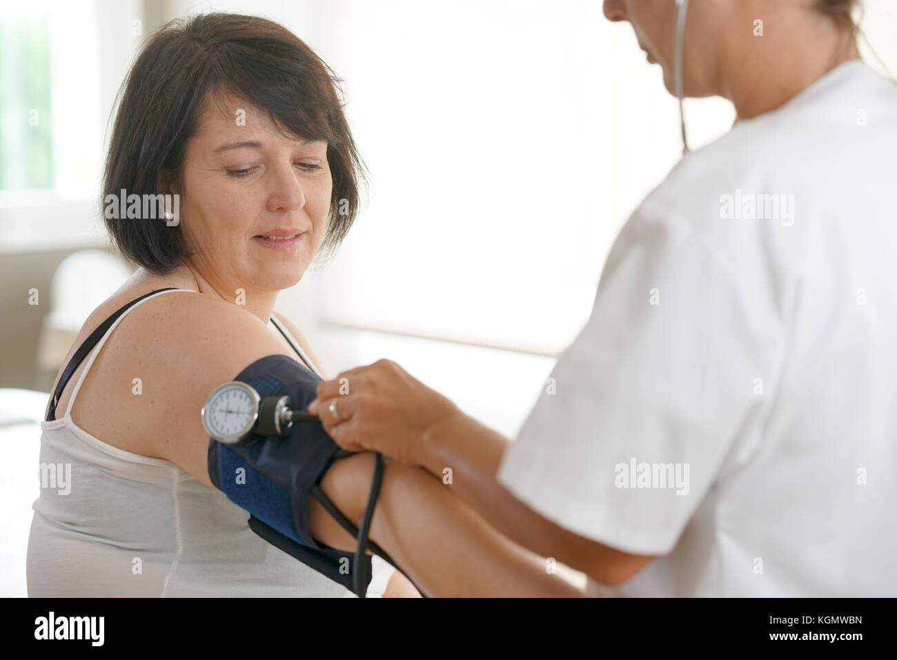 Mature woman at the doctor, controlling blood pressure - Stock Image