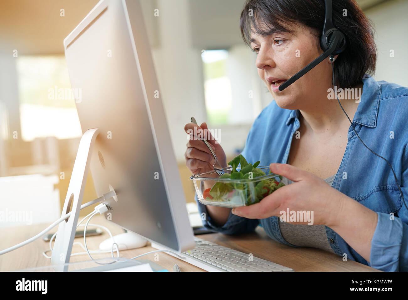 Telemarketing operator having lunch at work - Stock Image