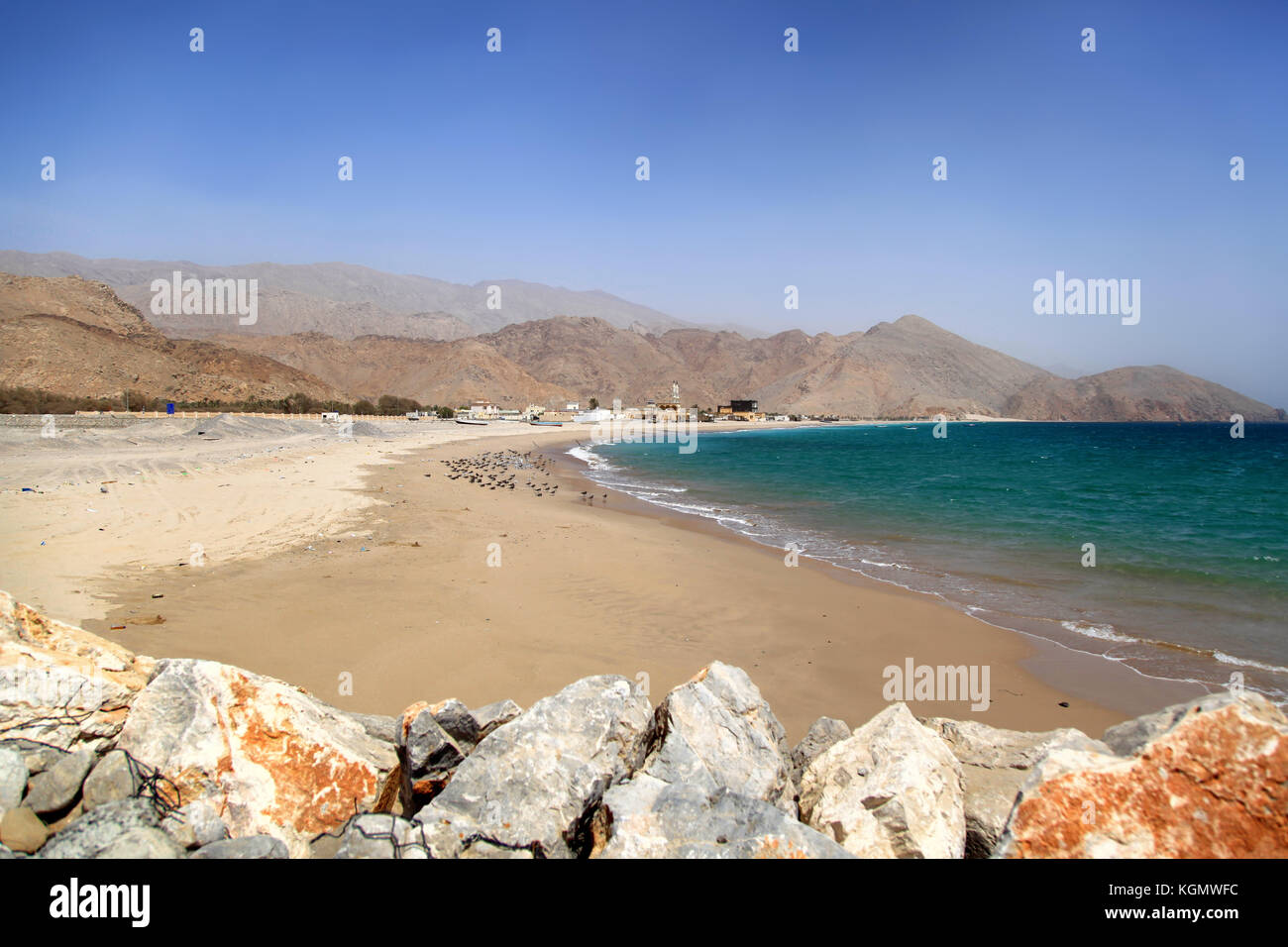 View on a dirty beach in Oman, sunny hot day, Al Hajar Mountains at the background, no people - Stock Image