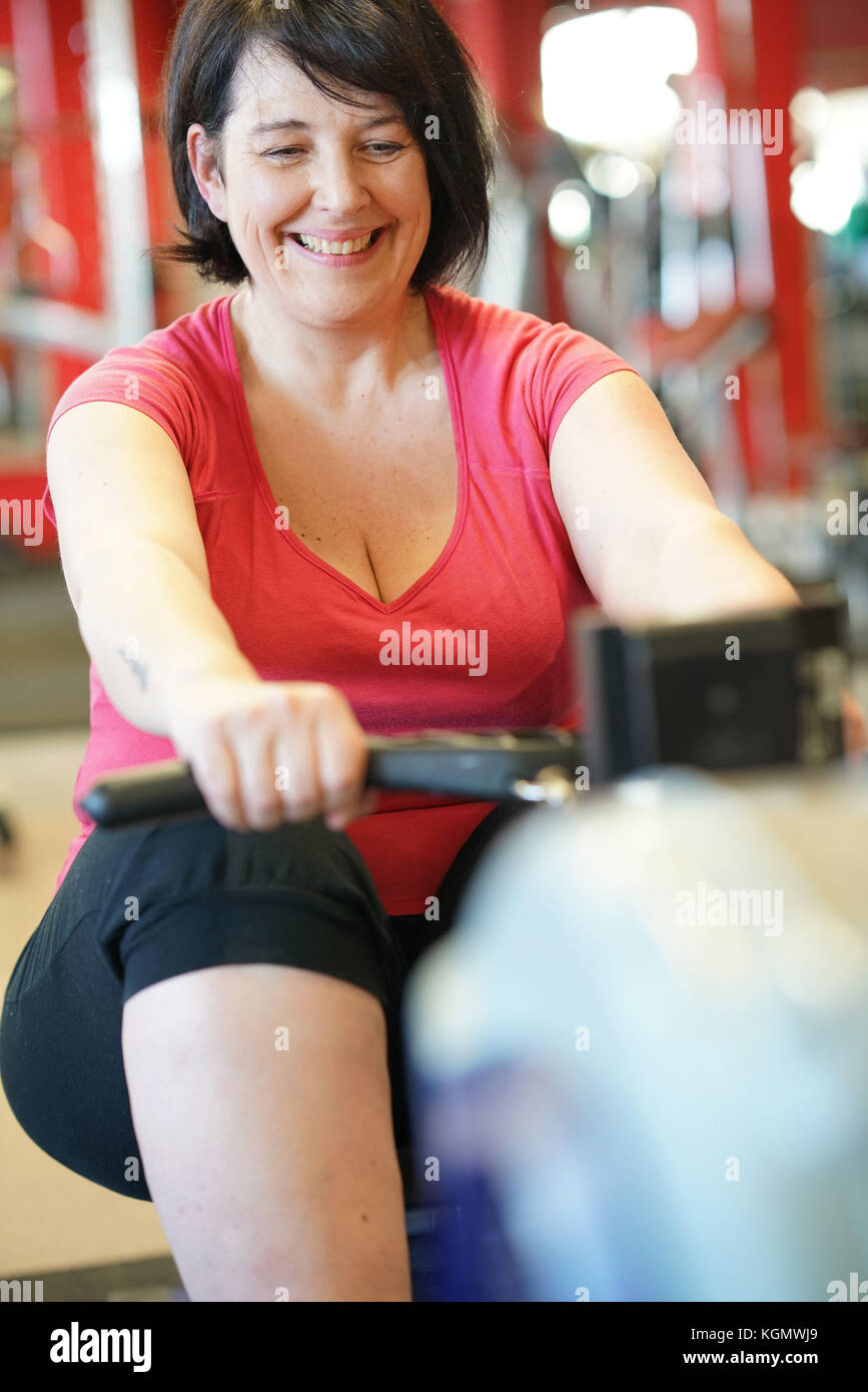 Overweight woman at the gym doing cardio exercises on rower - Stock Image
