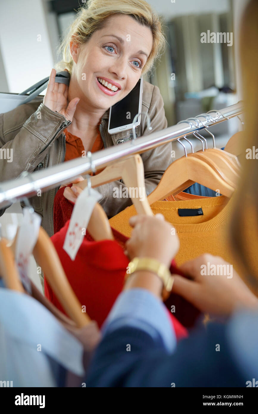 Woman talking on phone with friend while shopping in clothing store - Stock Image