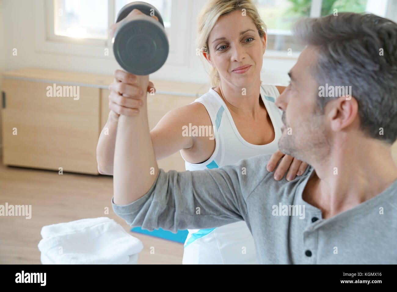 Physiotherapist strenghtening patient arms - Stock Image