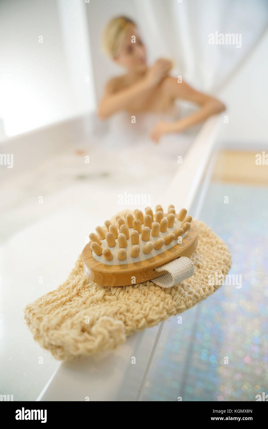 Closeup of massage gloves set on bathtub - Stock Image