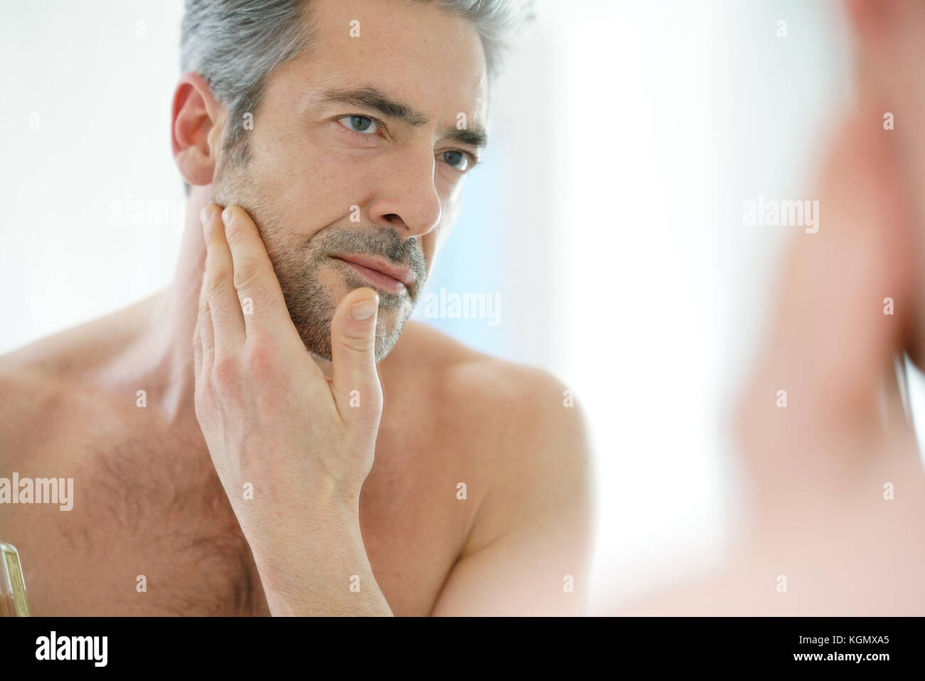 Portrait of mature man in front of mirror applying facial cream - Stock Image