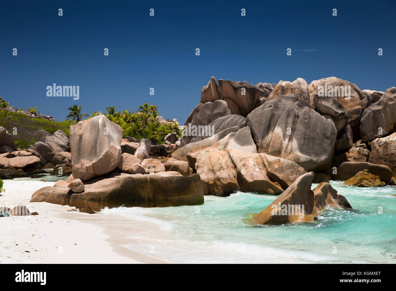The Seychelles, La Digue, Anse Cocos, beach, eroded granite rock formation in sea - Stock Image