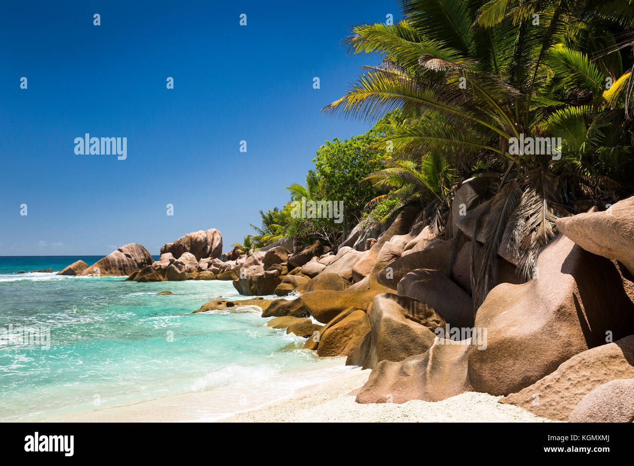 The Seychelles, La Digue, Petit Anse, beach, eroded granite rock formation in sea - Stock Image