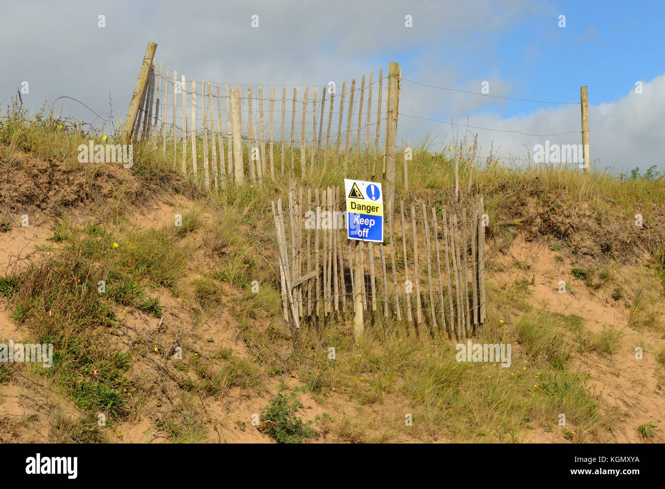Warning notice about a fenced off hazard in the sand dunes. - Stock Image