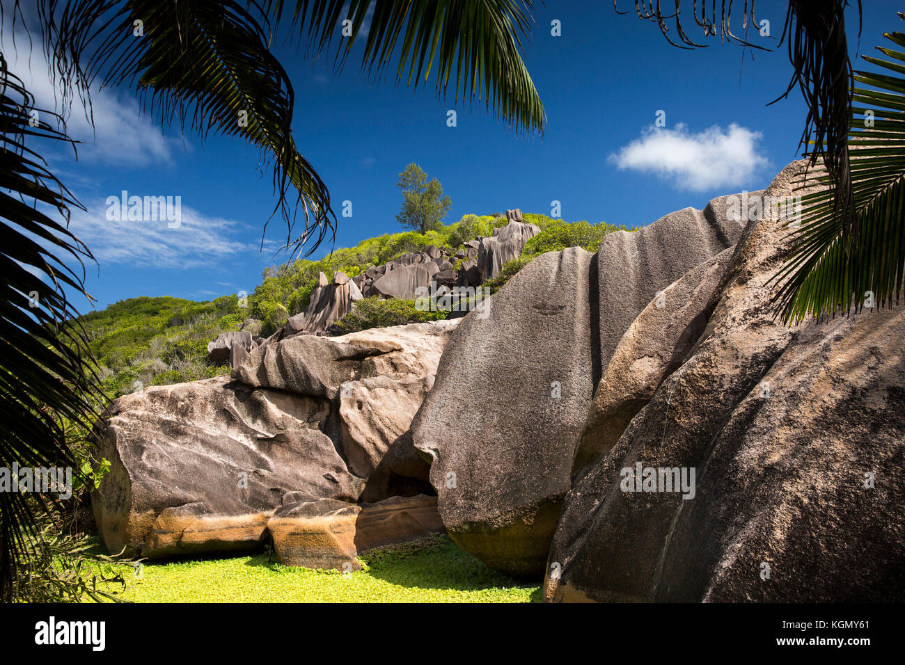 The Seychelles, La Digue, Grand Anse, eroded granite rock formation on hill behind beach - Stock Image