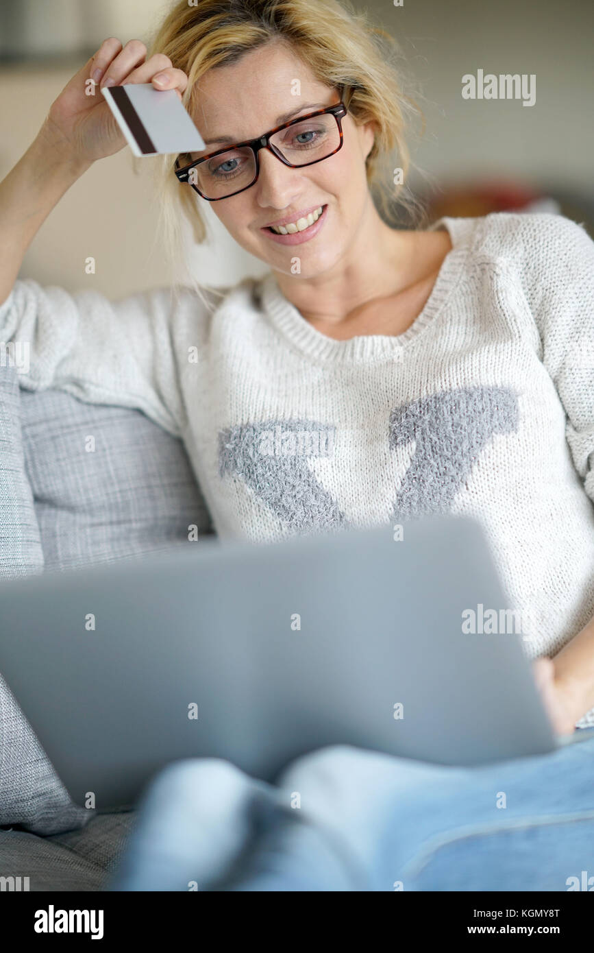 Middle-aged woman at home buying on internet with credit card - Stock Image