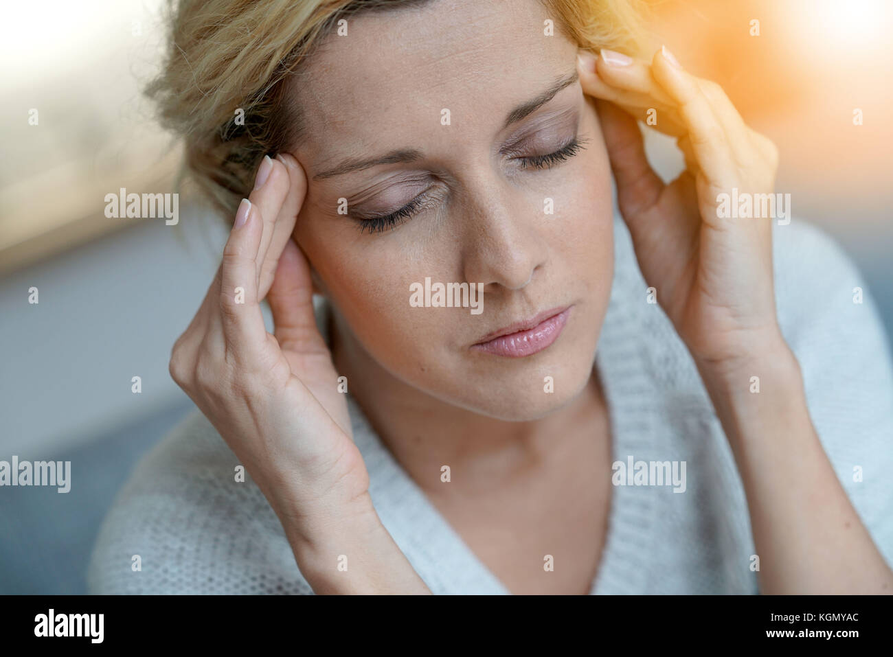 Portrait of middle-aged blond woman having a migraine - Stock Image
