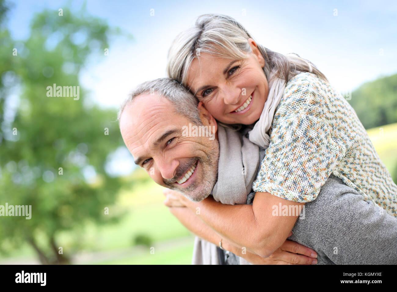 Senior man giving piggyback ride to woman - Stock Image