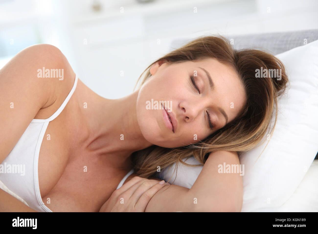 Closeup of woman asleep in bed - Stock Image