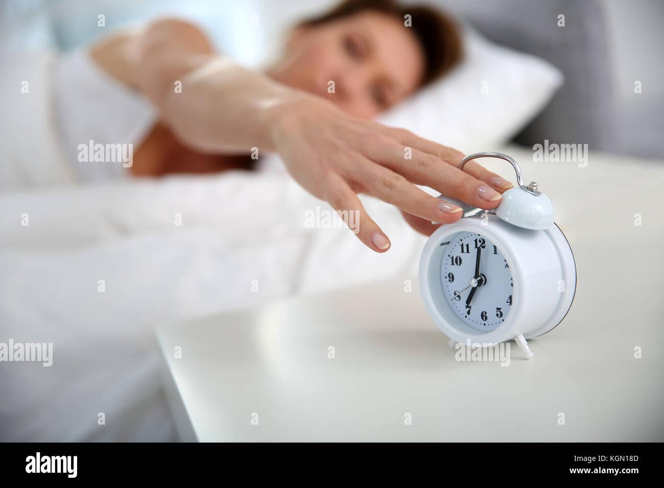 Woman turning alarm clock off in morning - Stock Image