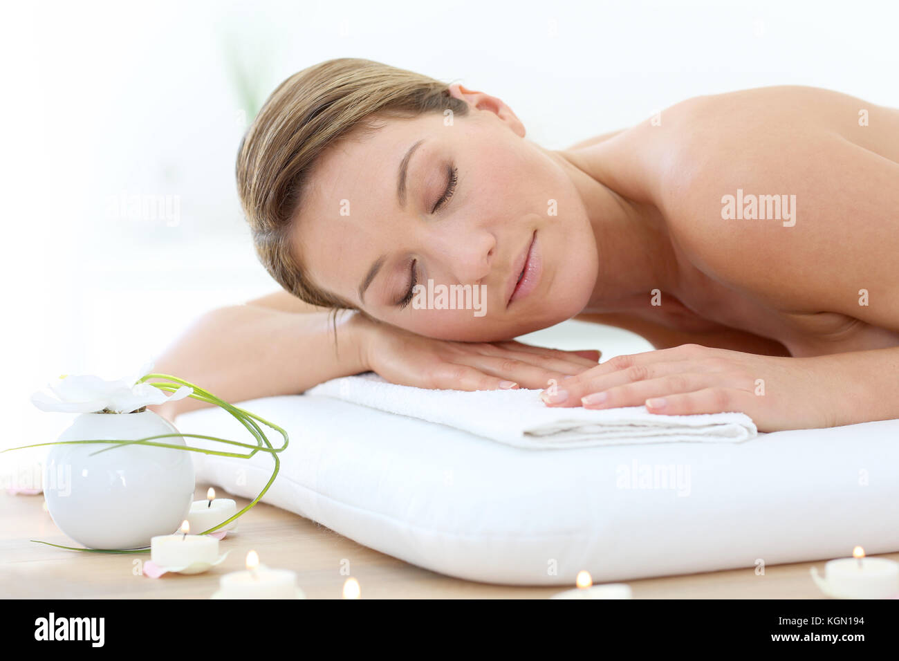 Attractive woman relaxing with eyes shut on massage bed - Stock Image