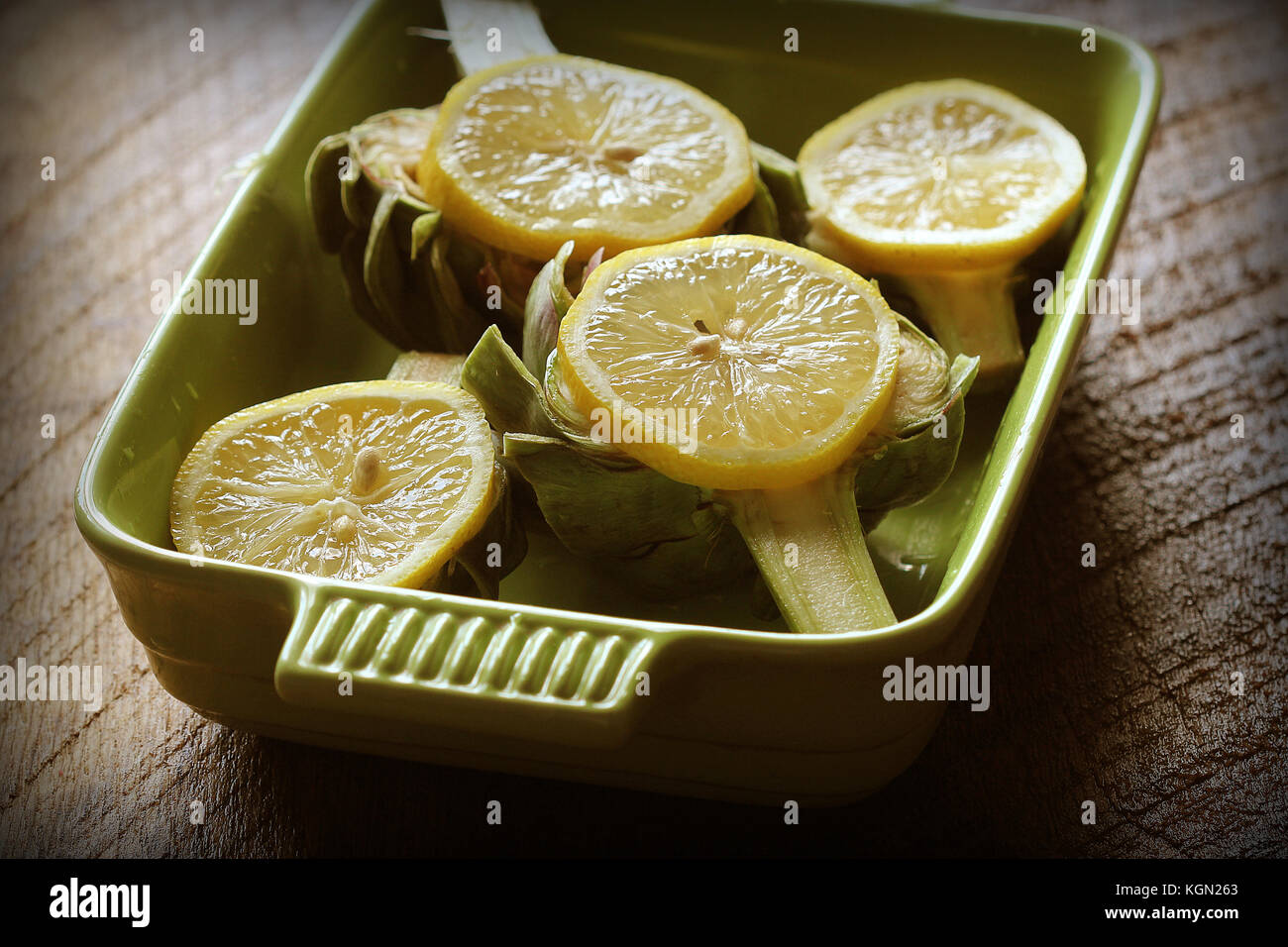 Artichokes recipe with garlic and lemon on pan . Ready for cooking - Stock Image