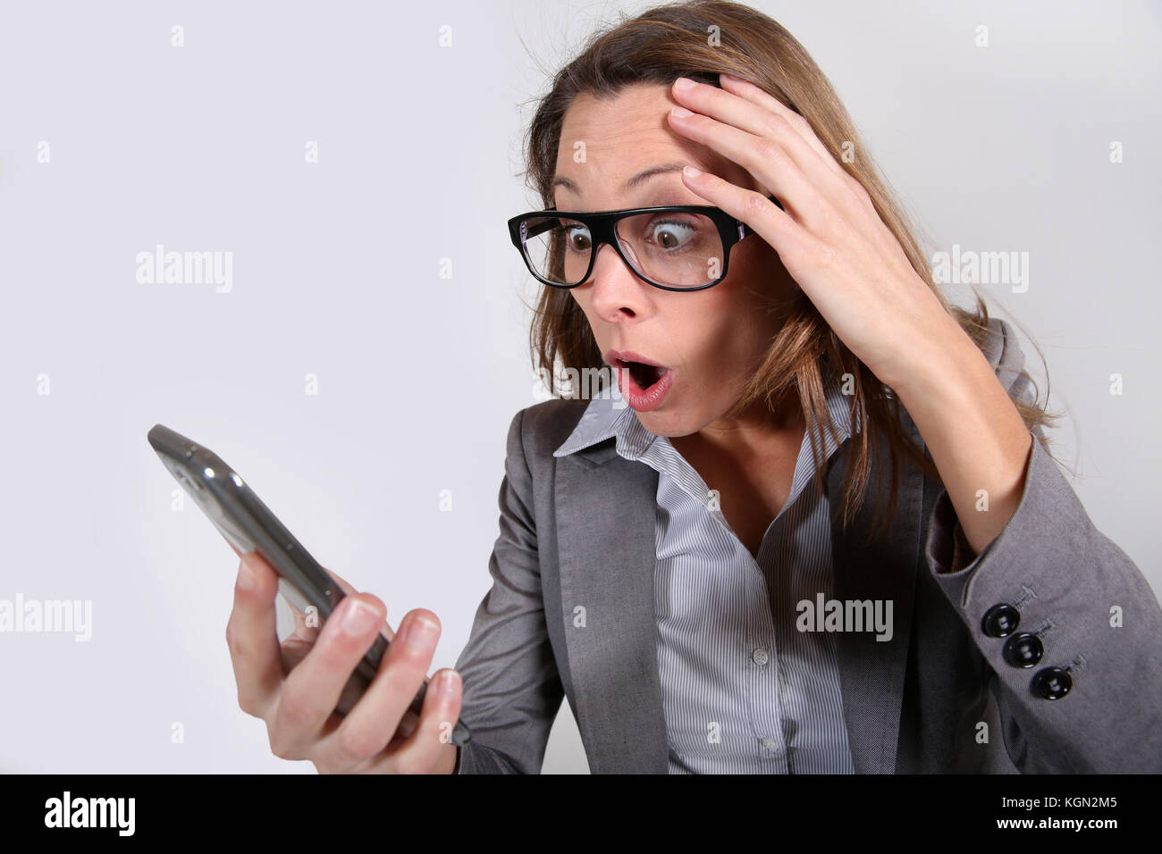 Businesswoman reading message on smartphone - Stock Image