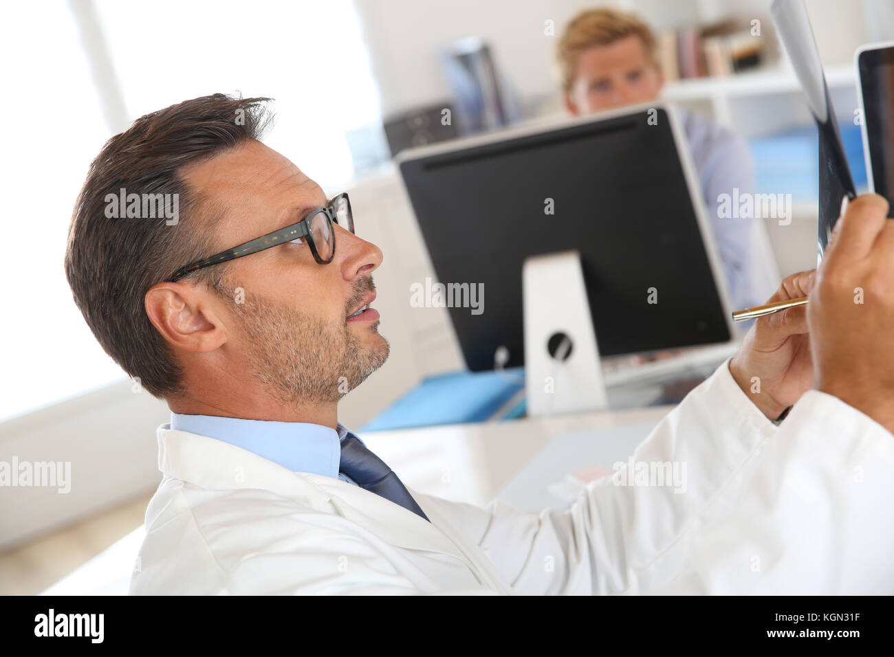 Doctor checking on X-Ray images - Stock Image
