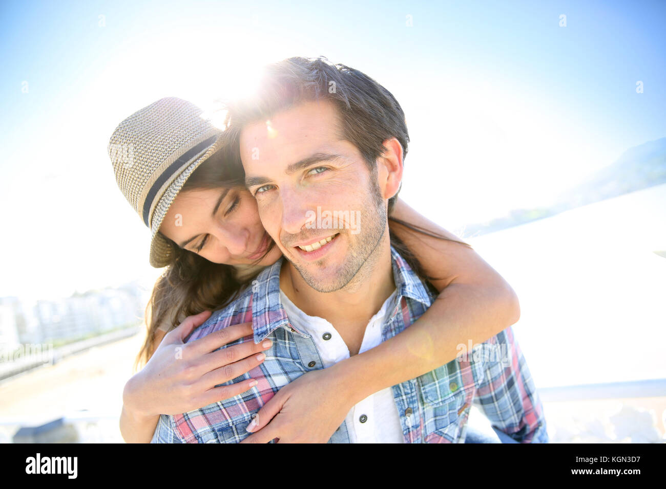 Man giving piggyback ride to girlfriend at the beach - Stock Image