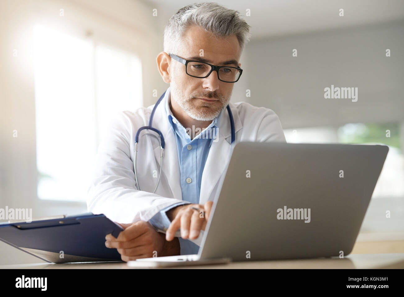 Doctor in office working on patient file - Stock Image