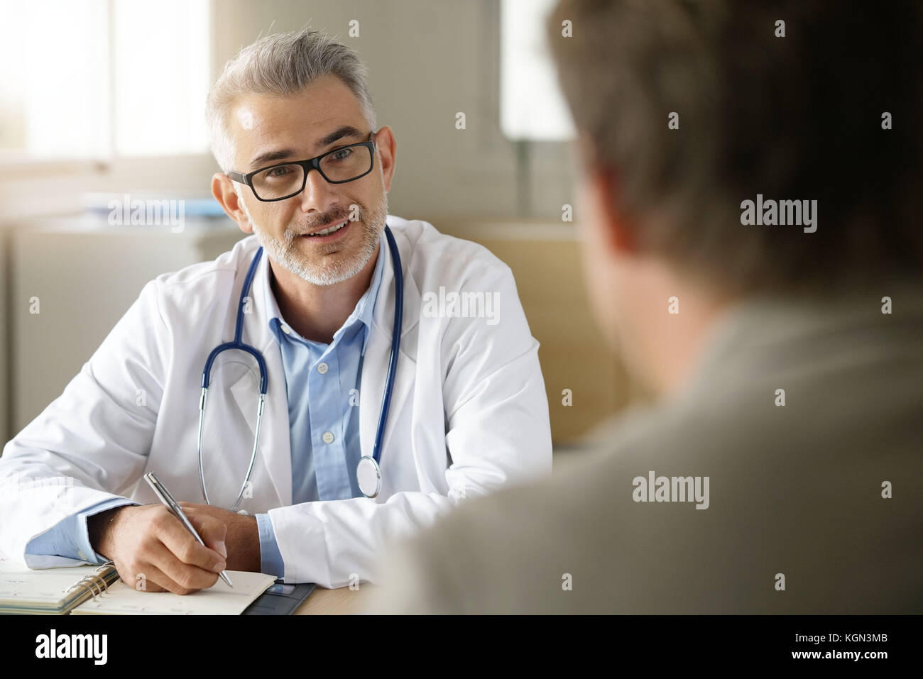 Doctor talking to patient in office Stock Photo