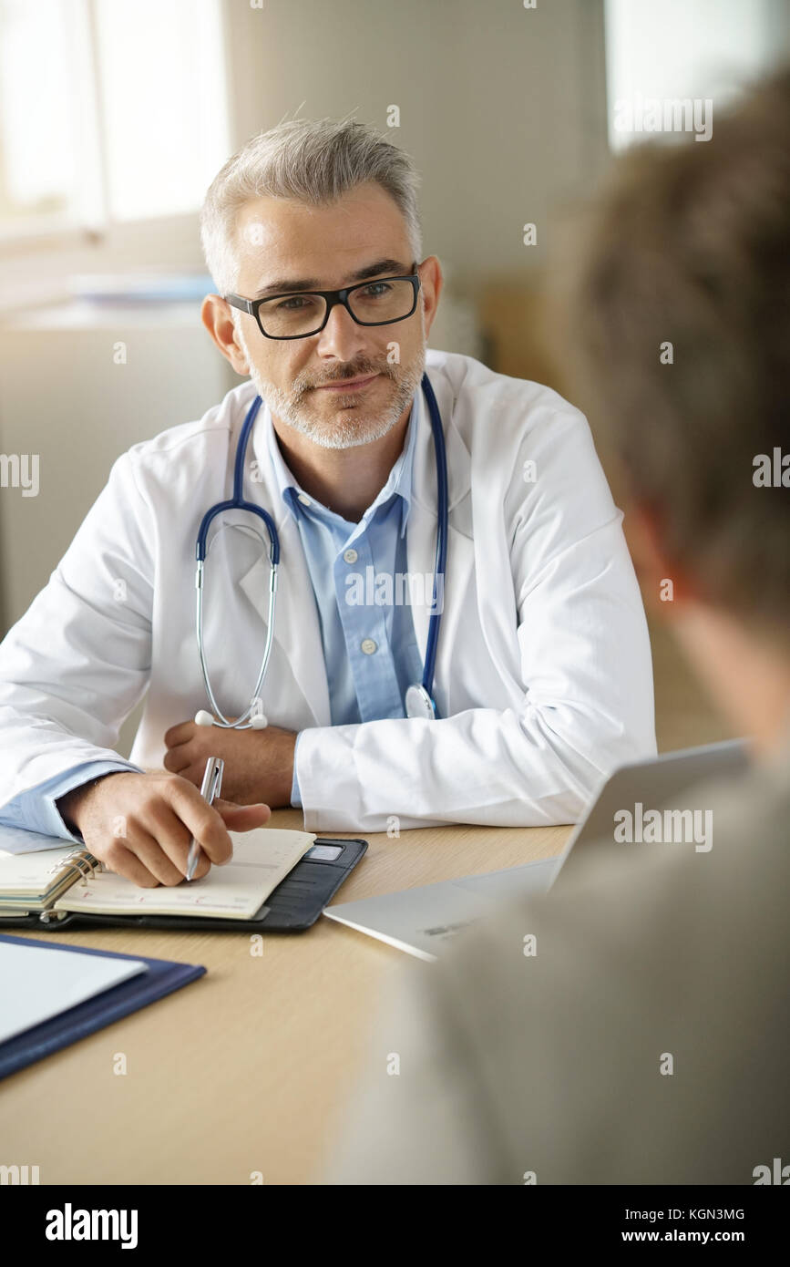 Doctor talking to patient in office - Stock Image