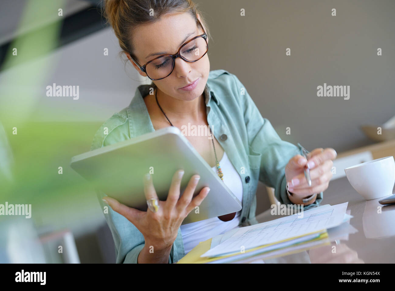 Trendy designer girl at home working on digital tablet - Stock Image