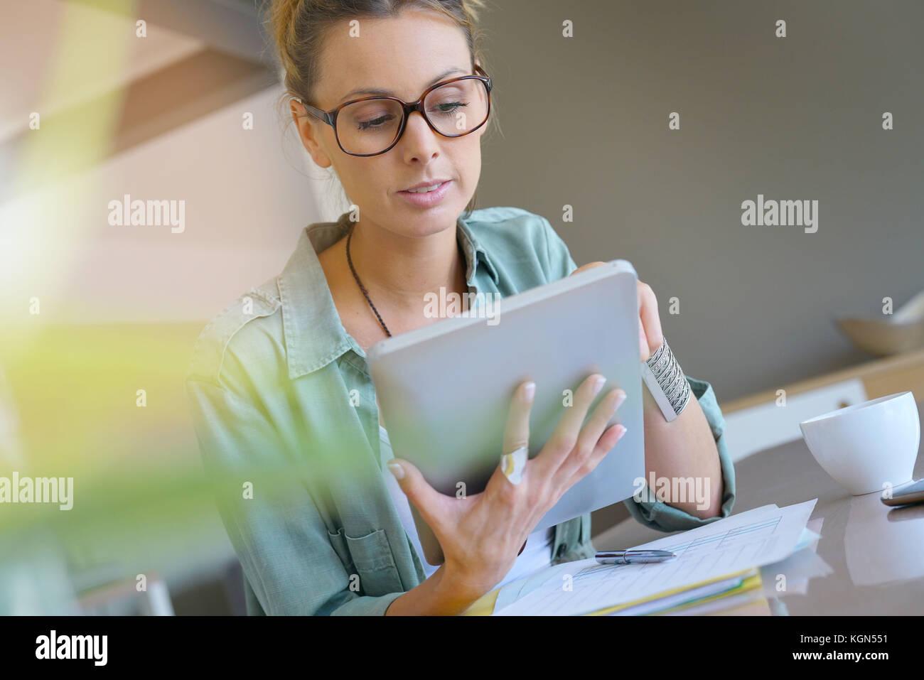 Trendy designer girl at home working on digital tablet - Stock Image