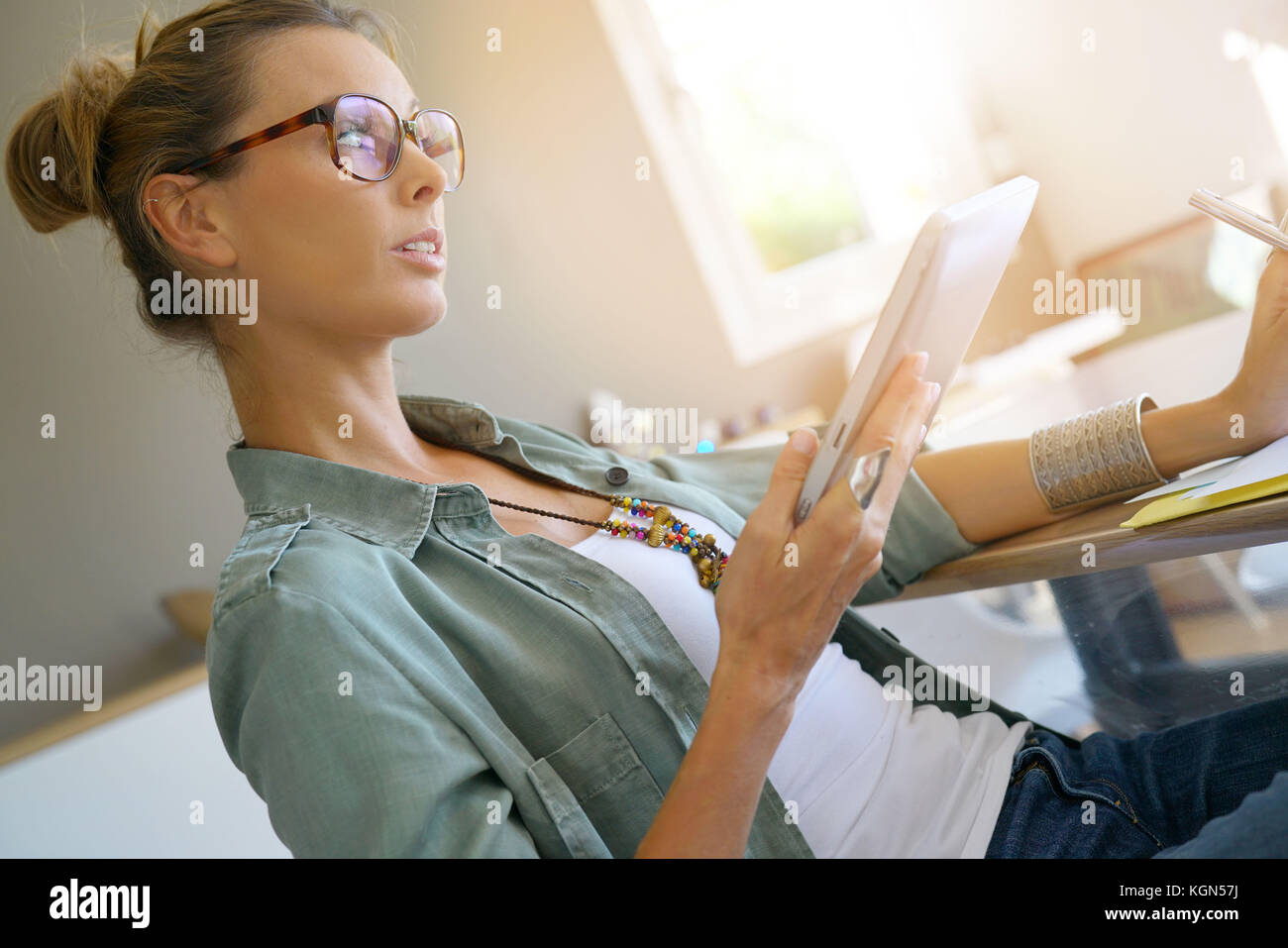 Trendy girl with eyeglasses connected on digital tablet - Stock Image